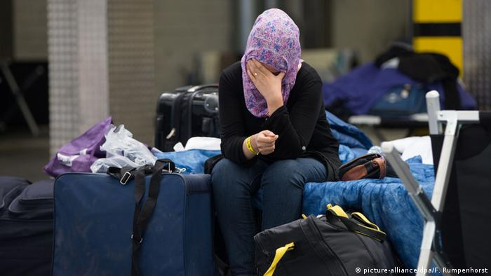 A refugee in a German shelter covers her face