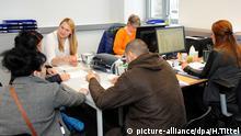 picture-alliance/dpa/H.Tittel Eine Mitarbeiterin (h.l.) nimmt am 03.03.2016 im neuen Ankunftszentrum des Bundesamts für Migration und Flüchtlinge (BAMF) in Trier (Rheinland-Pfalz) die Daten von Asylbegewerbern auf. Ziel des Ankunftszentrums ist die Aufnahme und Registrierung der Flüchtlinge sowie die Annahme und Bearbeitung der Asylanträge effiezient und schnell zu gestalten. Foto: Harald Tittel/dpa +++(c) dpa - Bildfunk+++