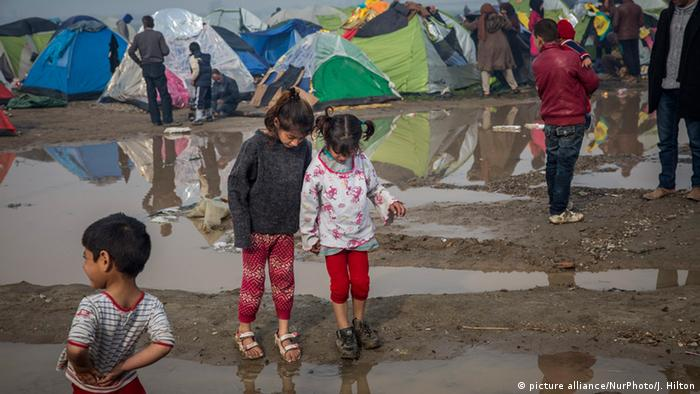 Refugee children play in puddles and mud that formed after a heavy rainfall the previous night. More than 13,000 people, mainly Syrian and Iraqi refugees, are trapped at the Idomeni border camp on the Greek side of the Greek/Macedonian border on March 8, 2015. (Photo by Jodi Hilton/NurPhoto)