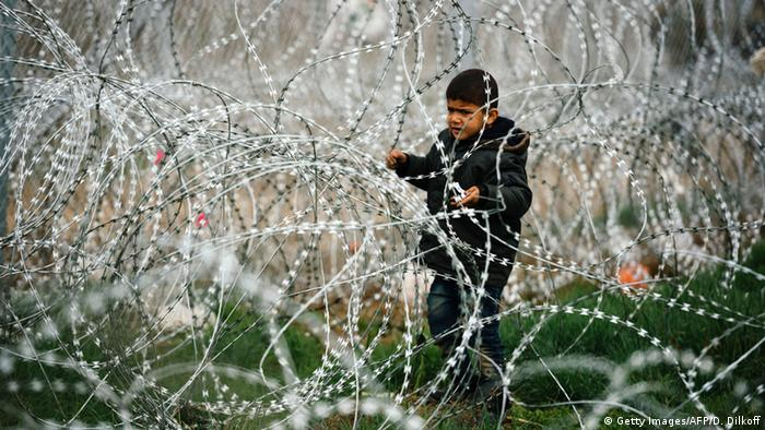 kid standing next to barbed wire fence © Getty Images/AFP/D. Dilkoff