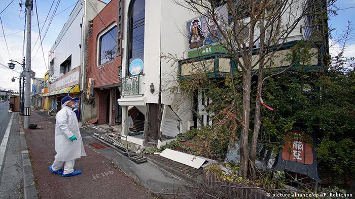Japan Fukushima Namie Mann mit Schutzanzug vor zugewachsenem Haus