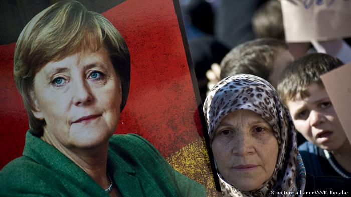 Syrian woman holds up a poster of Angela Merkel