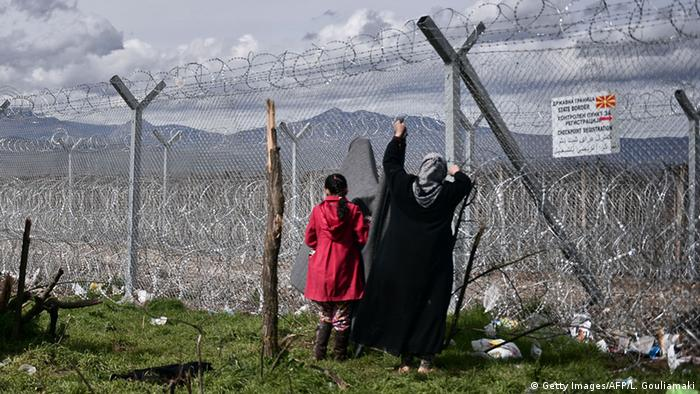 A woman hangs a blanket at the border fence of the Greek Macedonian borders, near the village of Idomeni on March 8, 2016, where thousands of refugees and migrants are stranded.