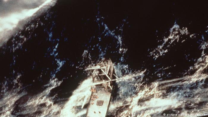 Un pequeño barco contra unas enormes olas.