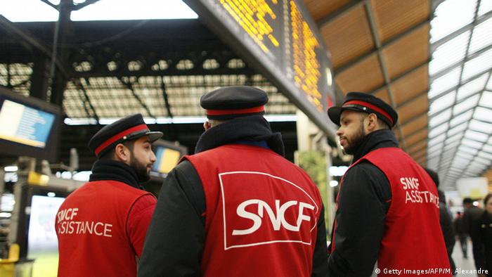 Employees of French railway operator SNCF gather as they guide commuters at the Saint Lazare railway station