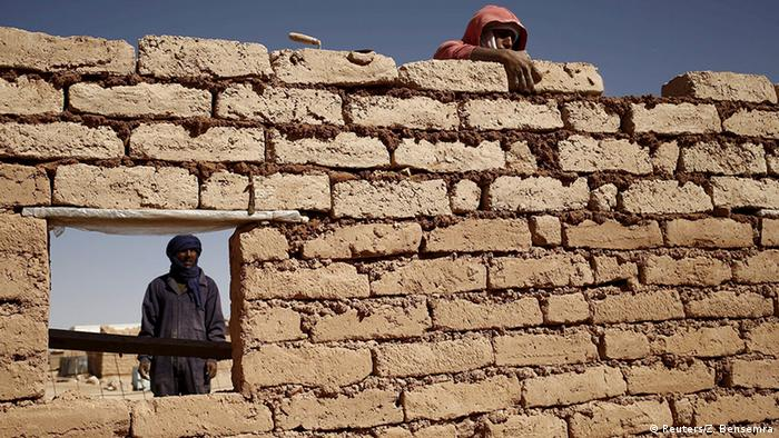 An indigenous Sahrawi man rebuilds his house, which was damaged by floods last October, in Al Smara desert refugee camp in Tindouf