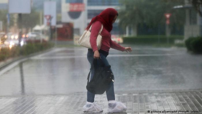 Una mujer se cubre de las lluvias en Dubai, Emiratos Árabes Unidos