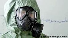 FILE - This image made from an AP video posted on Wednesday, Sept. 18, 2013 shows a student wearing a gas mask and protective suit during a session on reacting to a chemical weapons attack, in Aleppo, Syria. The Islamic State group is aggressively pursuing development of chemical weapons, setting up a branch dedicated to research and experiments with the help of scientists from Iraq, Syria and elsewhere in the region, according to Iraqi and U.S. intelligence officials. (AP Photo via AP video, File)