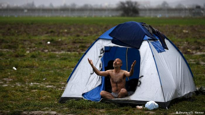 A migrant, who is waiting to cross the Greek-Macedonian border, reacts while being photographed at a makeshift camp near the village of Idomeni, Greece March 9, 2016.
