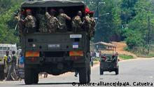 Mozambican troops inside a militray truck driving on a street.