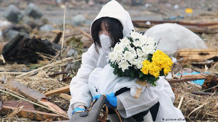 Fukushima Zerstörung Frau mit Blumen