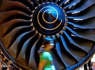 A woman walks past a Trent 900 engine