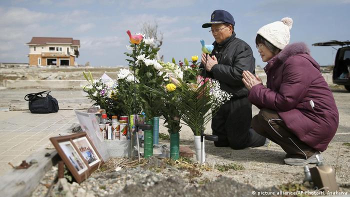 Menschen beten vor Blumen (Foto: ap)