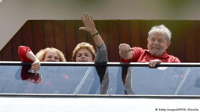 Lula da Silva and President Dilma Rousseff waves to supporters from the balcony of his house