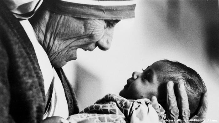 Indien Mutter Teresa mit einem armlosen Baby in Kalkutta (picture-alliance/AP Photo/E. Adams)