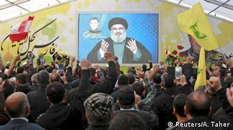 Лидер Хезболлах шейх Насралла обращается с экрана к своим сторонникам