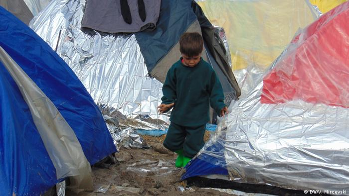 A child walks between tents at the makeshift Tabanovce camp
