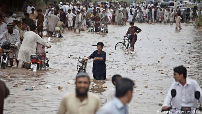 People push bicycles and mopeds and walk through a flooded street