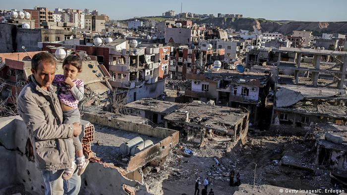 A man holds his daughter as he looks out at the ruined houses of Cizre (photo: Getty Images/C. Erdogan)