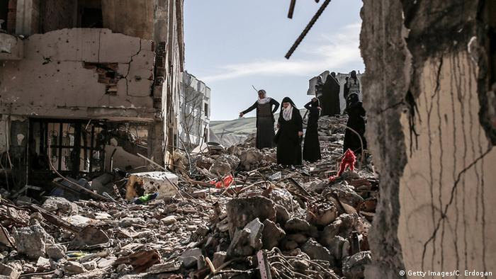 People walk past ruined houses and shops in Cizre (photo: Getty Images/C. Erdogan)