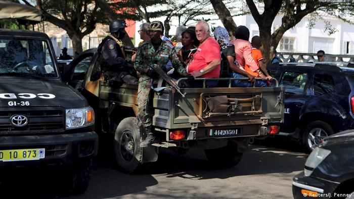 Security forces evacuate people in Bassam, Ivory Coast, March 13, 2016.