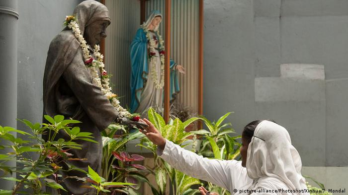 A nun touches the statue of Mother Teresa during her 105th birth anniversary at the Missionaries of Charity house in Kolkata, capital of eastern Indian state West Bengal, Aug. 26, 2015 (Photo: picture-alliance/Photoshot/Xinhua/T. Mondal)