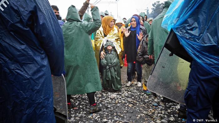 Two women stand with a child amid a crowd of people in rain gear