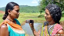 A woman speaks into a mobile phone held by another woman