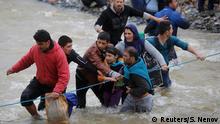 14.03.2016+++ Migrants wade across a river near the Greek-Macedonian border, west of the the village of Idomeni, Greece, March 14, 2016. REUTERS/Stoyan Nenov +++ (C) Reuters/S. Nenov