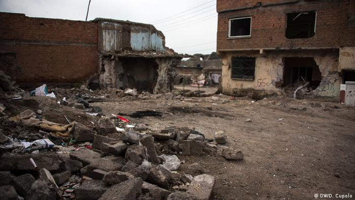 A burnt-out building and rubble are seen