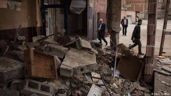 Pedestrians walk past a building of rubble