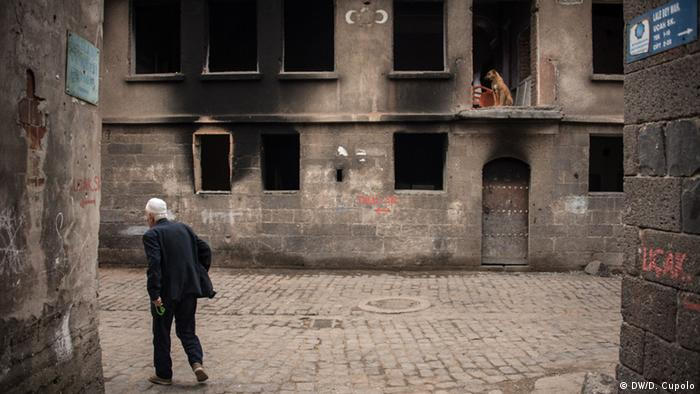 A man walks past a burnt-out building