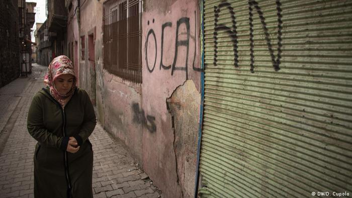 A woman walks past graffiti that reads Ocalan