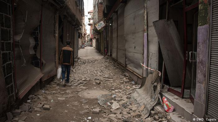 A man walks through a long street of damaged buildings