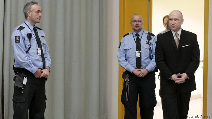 Anders Behring Breivik is escorted by prison guards as he arrives at the court room in Skien prison
