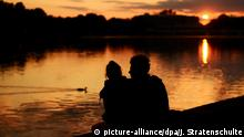 ARCHIV 2012 **** - Die Silhouette eines Paares zeichnet sich am 27.05.2012 am Maschsee in Hannover vor dem vom Sonnenuntergang rötlich verfärbten Abendhimmel ab. Foto: Julian Stratenschulte/dpa (zu Psychologin: Frühlingsgefühle hängen mit der Wahrnehmung zusammen vom 29.02.2016) +++(c) dpa - Bildfunk+++ © picture-alliance/dpa/J. Stratenschulte
