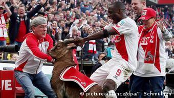 Anthony Ujah, atacante do Colônia, comemora gol em vitória sobre o Frankfurt por 4 a 2 pegando nos chifres de Hannes VIII em 2015