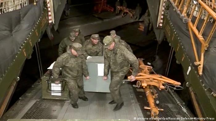 soldiers loading a cargo plane copyright: picture-alliance/dpa/Russian Defense Ministry Press