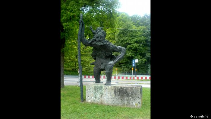 a bronze statue of St Cristopher on a concrete pedestal, in a park Alexander Fischer
