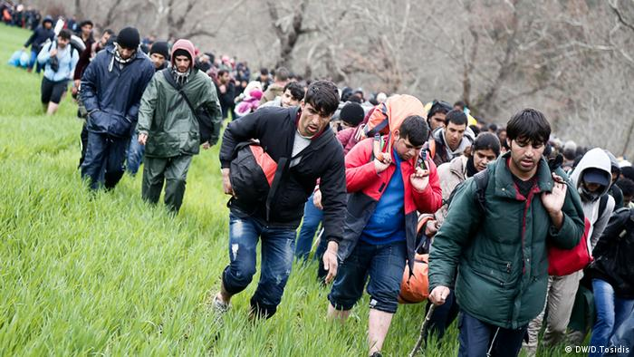 Migrants crossing a river to get to the Greek-Macedonian border