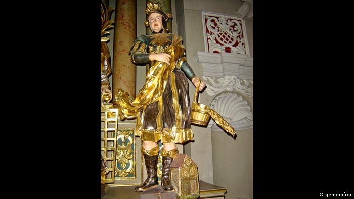 The statue of St. Florian, wearing a Roman soldier's uniform and carrying a bucket of water
