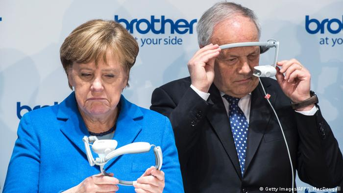 Анґела Меркель та Йоганн Шнайдер-Амманн розглядають окуляри доповненої реальності