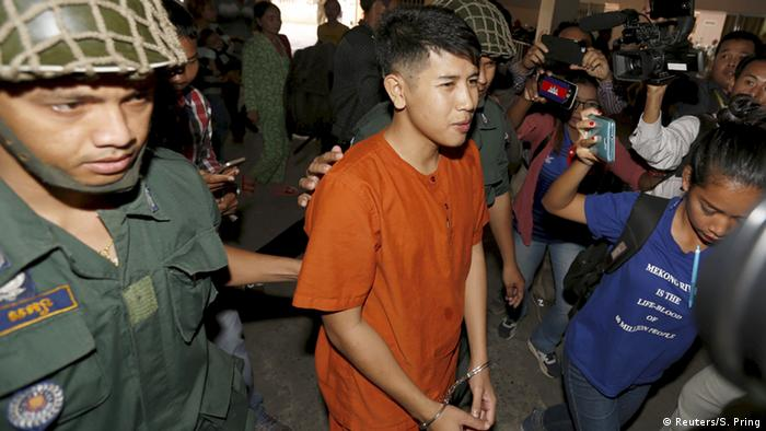 Pro-democracy advocate Kong Raya, wearing an orange jump suit, is held by the arm and escorted in court by a Cambodian police officer wearing a helmet, and wearing military fatigue.