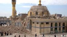 Iraqis walk past the damaged shrine following an explosion in Samarra, 95 kilometers (60 miles) north of Baghdad, Wednesday, Feb. 22, 2006. A large explosion Wednesday heavily damaged the golden dome of one of Iraq's most famous Shiite religious shrines, sending protesters pouring into the streets. It was the third major attack against Shiite targets in as many days. (AP Photo/Hameed Rasheed)