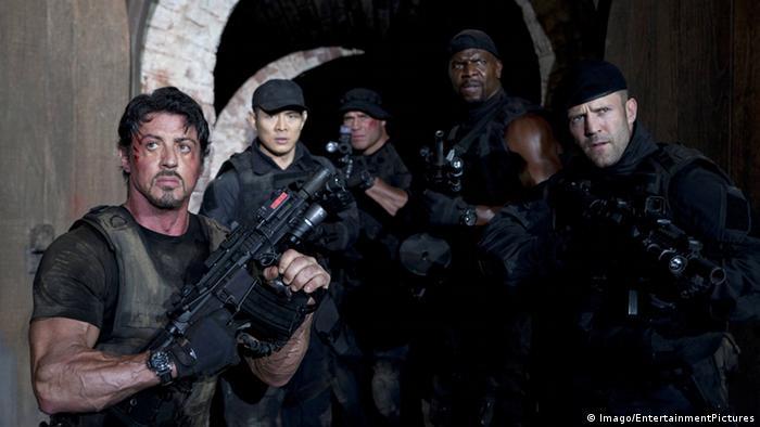 Auf dem Bild sind fünf schwer bewaffnete Männer zu sehen. Links steht Stallone.