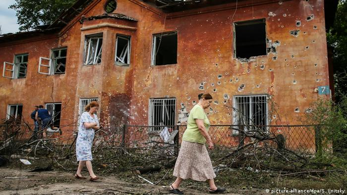 Women in Ukraine walk passed a house damaged in a shelling by the Ukrainian army