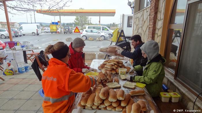 Freiwillige Helfer verteilen im Flüchtlingslager Idomeni an der griechische-mazedonischen Grenze Brot (Foto: DW/Panagiotis Kouparanis)