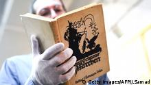 Marcho Tomaschett of Swann Auction Galleries shows Anne and Margot Frank's copy of Grimm's Fairy Tales, at their gallery in New York on March 16, 2016. The book of fairytales owned and signed by the German-Jewish diarist Anne Frank who perished in the Holocaust is being offered at auction in New York, valued at $20,000 to $30,000.The worn edition of Grimms stories, Aus Grimms Marchen, was published in 1925 in Vienna. It belonged to Frank and her sister Margot before they went into hiding in Amsterdam in 1942 to escape the Nazi occupation. / AFP / Jewel SAMAD (Photo credit should read JEWEL SAMAD/AFP/Getty Images) Getty Images/AFP/J.Samad
