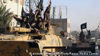 In this undated file image posted by the Raqqa Media Center in Islamic State group-held territory, on Monday, June 30, 2014, which has been verified and is consistent with other AP reporting, fighters from the Islamic State group ride tanks during a parade in Raqqa, Syria.