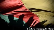 31.07.2015 ARCHIV - Kurdische Demonstranten zeichnen sich am 01.11.2014 in Hannover (Niedersachsen) während einer Demonstration durch die Innenstadt gegen die Terrormiliz Islamischer Staat als Silhouette auf der Fahne der Partei der Demokratischen Union (PYD) ab. Foto: Alexander Körner/dpa (zu lrs Kurden und Türken in Rheinland-Pfalz vom 31.07.2015) +++(c) dpa - Bildfunk+++ (c) picture-alliance/dpa/A. Körner